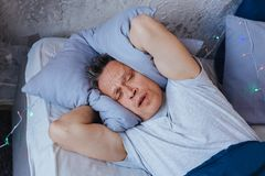 Exhausted mature man wanting sleep. Morning again. Displeased mature man lying on bed and squeezing pillow stock photography