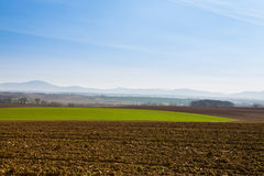 Morning on agricultural fields. Sunny spring day with blue sky above cultivated land with fields and hills in the background Stock Image