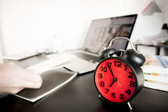 Morning Alarm clock on working computer desk. Red Morning Alarm clock on working computer desk Stock Photography