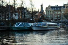 Morning in Amsterdam. Water street with boats on the pier, reflected in quiet water. stock photography