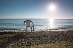 In morning ashore white empty plastic chair costs Stock Images