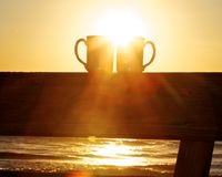 Morning on the Atlantic. Two silhouetted coffee mugs sitting on railing in golden light, sun rising, with ocean waves in the background Royalty Free Stock Photo