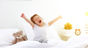 Morning awakening child girl in bed Stock Photos