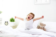 Morning awakening child girl in bed Stock Photography