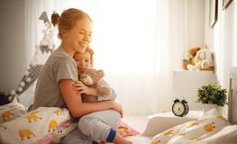 Mother wakes her daughter in bed in  morning Royalty Free Stock Image
