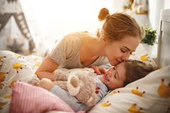 Mother wakes her daughter in bed in  morning Stock Photography