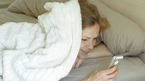 Morning. Awakening women in bed. Sleeping young woman with red hair in bed peeking out from under the blanket, looking at the phone screen and smiling, woke up stock footage