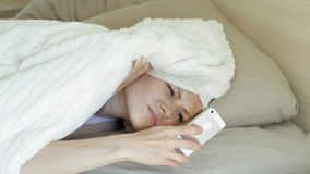 Morning. Awakening women in bed. Sleeping Young woman with red hair in bed peeking out from under the blanket, looking time on the phone, hiding and continuing stock video