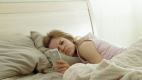 Morning. Awakening women in bed. Sleeping Young woman with red hair in pink clothes in bed is looking at the time on the phone and continues to sleep. Morning stock video