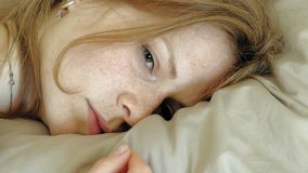 Morning. Awakening women in bed. Sleeping young woman with red hair in pink clothes on the bed wakes up and opens eyes, close-up of eyes. Morning stock footage