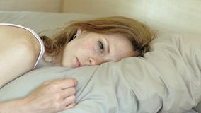 Morning. Awakening women in bed. Sleeping young woman with red hair in pink clothes on the bed wakes up, opens her eyes and smiles, close-up of the eyes stock footage