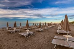 Morning on the beach with empty chaise lounges. Italy stock photo