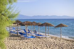 Morning at a beach with loungers under palm tree leaves umbrellas. Ierissos, Greece. Early day at beautiful Ierissos beach in Greece with loungers under palm stock photo