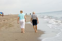 Morning Beach walk. A senior husband and wife walk in the water's edge while strolling the Florida beach stock image