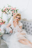 The morning of a beautiful bride dressed in a peignoir. Portrait of a bride in a peignoir sitting on the couch with a beautiful hairdo and makeup Stock Photos