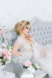 The morning of a beautiful bride dressed in a peignoir. Portrait of a bride in a peignoir sitting on the couch with a beautiful hairdo and makeup stock photo