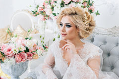 The morning of a beautiful bride dressed in a peignoir surrounded by flowers. Portrait of a bride in a peignoir sitting on the couch with a beautiful hairdo and Stock Images