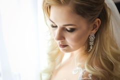 Close up photo of a bride standing in front of the window. Morning of a beautiful bride in a white wedding dress standing in front of the light window Royalty Free Stock Photography
