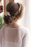 Morning beautiful happy young girl of the bride near a window in a white dress with a beautiful boudoir evening festive hairdo wit Stock Image