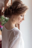Morning beautiful happy young girl of the bride near a window in a white dress with a beautiful boudoir evening festive hairdo wit Royalty Free Stock Photos