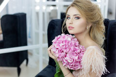 Morning of a beautiful tender sweet bride in a boudoir dress with a bouquet of hydrangea flowers with an evening hairdo and bright. Make-up in the studio Royalty Free Stock Photo