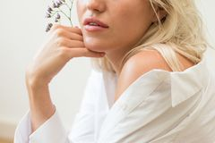 Portrait of a blonde woman. Lips. Holding flowers stock photo