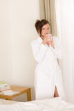 Morning bedroom - woman in bathrobe with coffee Stock Photography
