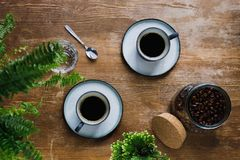 Morning black coffee in cups. On table with plants in coffee shop Stock Image