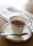 Morning black tea. With newspaper Royalty Free Stock Photos