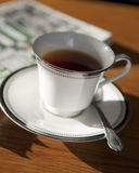 Morning black tea. With newspaper royalty free stock image