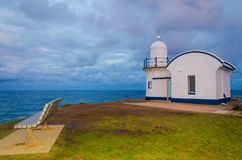 Small lighthouse on top of the hill during morning sunrise stock image