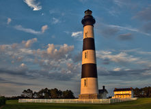 Morning at Bodie Island Lighthouse. The lighthouse and lightkeeper's house are illuminated in the early morning light at the Bodie Island Lighthouse in the Outer Royalty Free Stock Images
