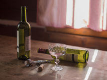Morning after booze-up two empty bottles of red wine and glass t Royalty Free Stock Photography