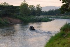 Morning on the boundary Menammey river. Burmans by the boat are illegally transported on the Thai side, Myanmar Stock Photo