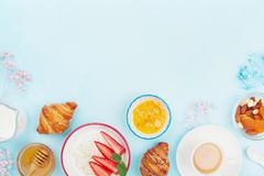 Morning breakfast with coffee, croissant, oatmeal, jam, honey and fruit on blue table top view. Flat lay style. Stock Photo