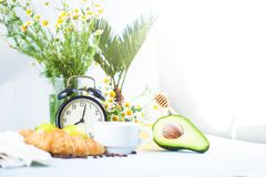 Morning breakfast ,coffee in a white cup Croissant Avocado Awakening with an alarm clock Cheerful, healthy breakfast fresh Copy sp royalty free stock image