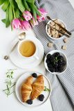 Morning breakfast with cup of coffee, croissants, fresh berries and pink flowers tulips. On white tray, brown sugar royalty free stock photos