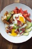 Morning Breakfast. Eggs over medium, tomato, avocado, bacon, and potatoes Stock Images