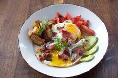 Morning Breakfast. Eggs over medium, tomato, avocado, bacon, and potatoes Royalty Free Stock Photography