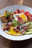 Morning Breakfast. Eggs over medium, tomato, avocado, bacon, and potatoes Royalty Free Stock Images