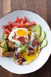 Morning Breakfast. Eggs over medium, tomato, avocado, bacon, and potatoes Stock Photography