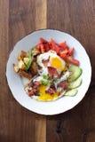 Morning Breakfast. Eggs over medium, tomato, avocado, bacon, and potatoes Royalty Free Stock Photo