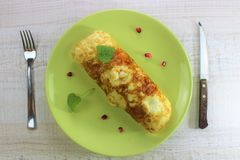 Morning breakfast eggs roll on a green plate fork and knife stock photo