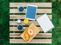 Morning Breakfast In Green Garden With French Croissant, Coffee Cup, Orange Juice, Tablet and Notes Book On Wood Table Stock Images