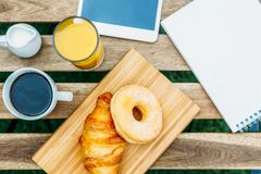 Morning Breakfast In Green Garden With French Croissant, Coffee Cup, Orange Juice, Tablet and Notes Book On Wood Table Stock Image