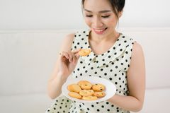 Morning breakfast. Happy girl eating cookie sitting on a couch a. T home Royalty Free Stock Photo