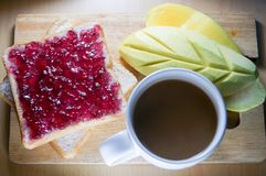 Breakfast time blueberry sandwich and coffee and mango. Morning breakfast have blueberry jam on brown bread with mango and coffee. It is healthy food and good Royalty Free Stock Photo