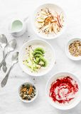 Morning breakfast inspiration - coconut overnight oatmeal with various topping. Healthy gluten free food concept. Top view Royalty Free Stock Photography