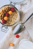 Morning breakfast, oatmeal with red and yellow raspberries and walnuts in a glass ja Royalty Free Stock Image