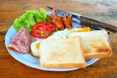 Morning breakfast with sausage, bacon, eggs and toast on wooden table Royalty Free Stock Image